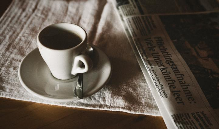 An image of a coffee cup on a table, next to a newspaper.