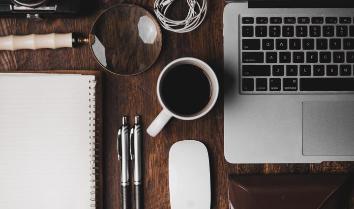 An image of a laptop, a cup of coffee, pens, and accessories, on a wooden table.
