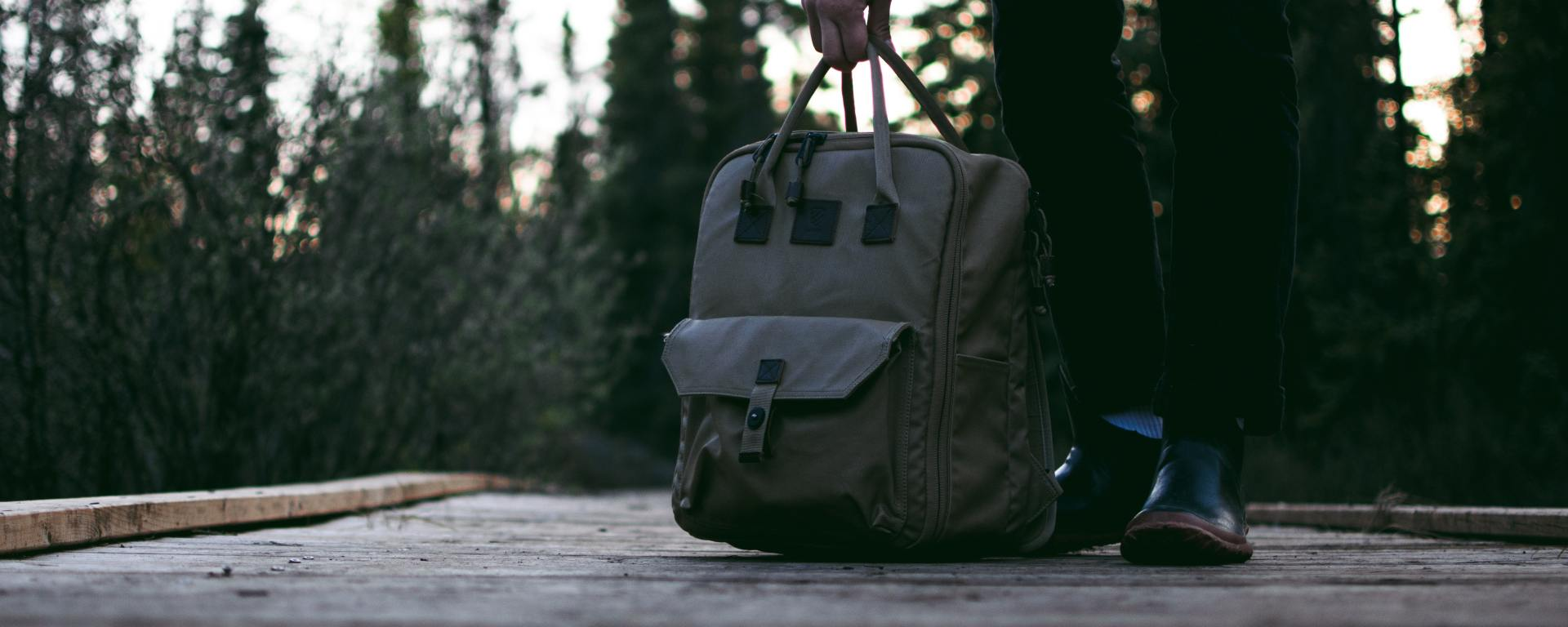 An image of a man's hand holding a backpack, resting on a wooden deck.