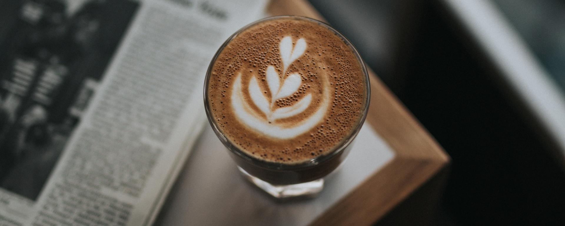 An image of a latte with froth art, sitting on a table next to a newspaper.