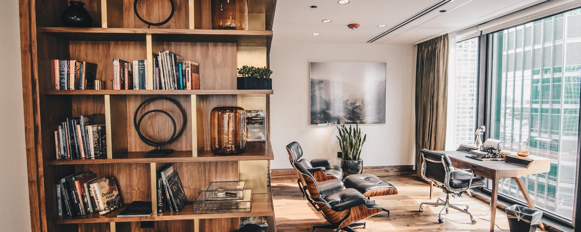 An image of an interior with living space, desk, and shelving, in medium wooden furnishings.