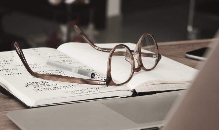 An image of an open notebook with a pair of glasses on top.
