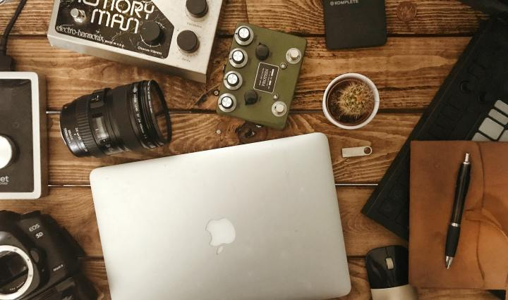 An image of a macbook, camera lens, soundboard,and notebook, on a wooden desk.