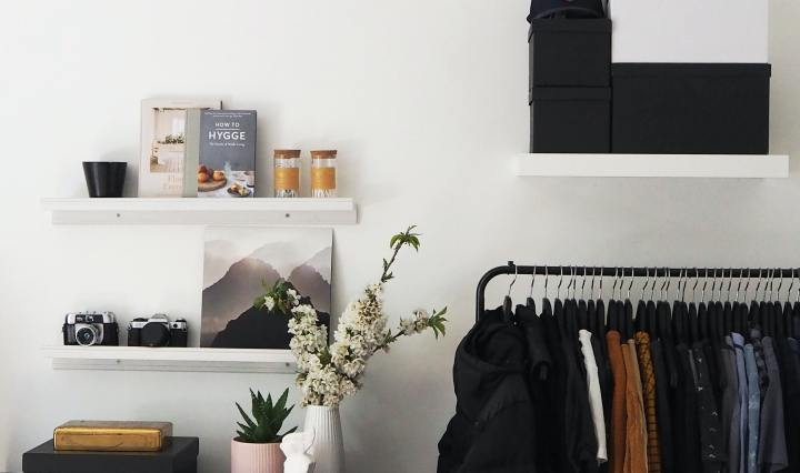 An image of a clothing rail with neatly lined shirts, next to a desk with potted plants atop it.