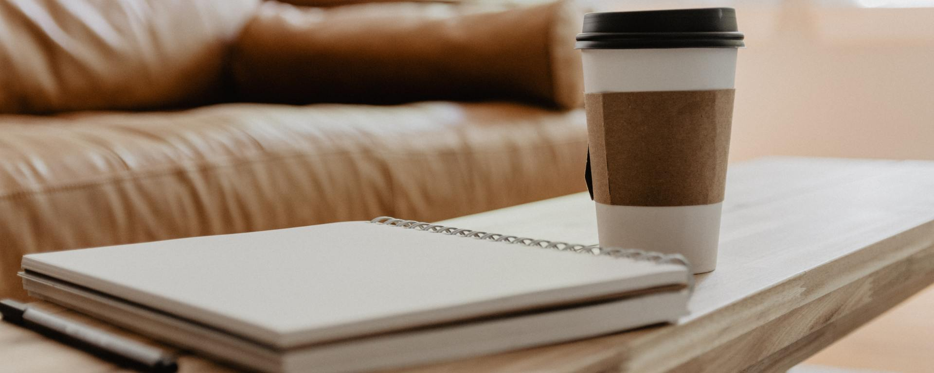 An image of a notebook and paper coffee cup on top of a wooden table.