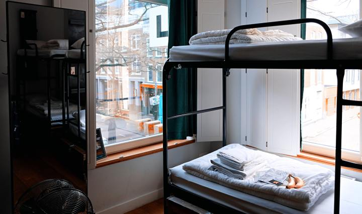 An image of a bunk bed in a hostel dorm with windows looking out onto a street.