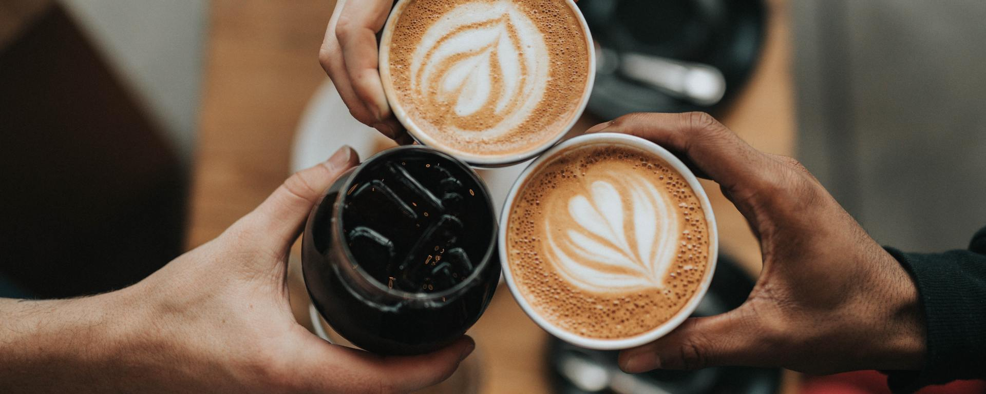An image of three people holding drinks.