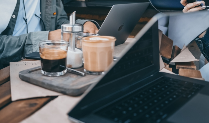 An image of coffee cups on a table with laptops.