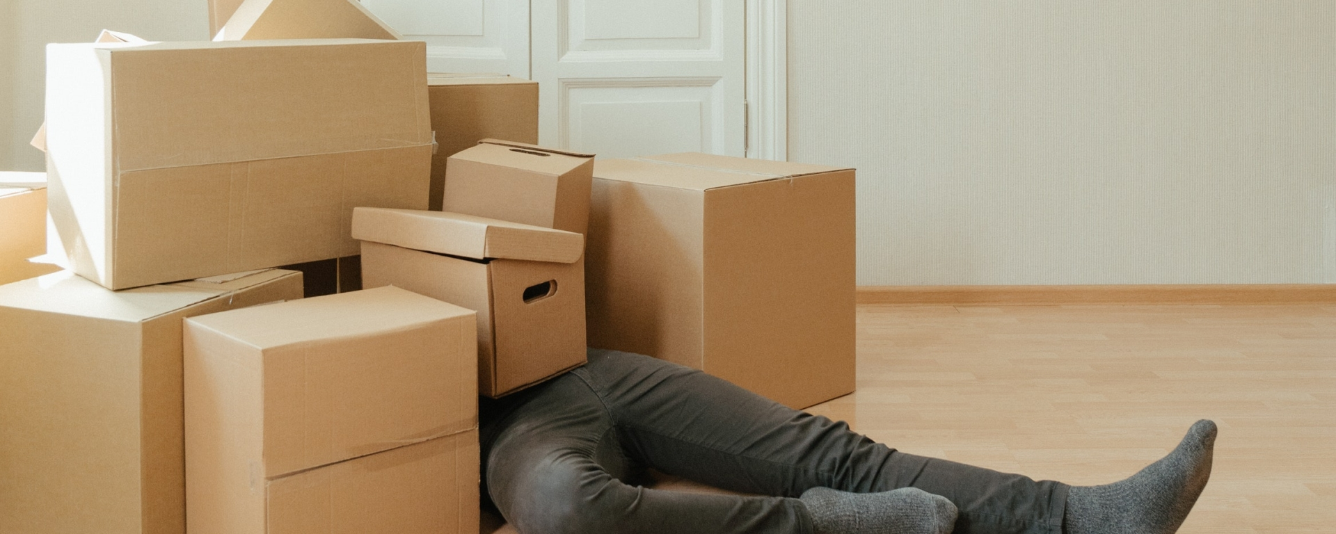 An image of a pile of boxes with a man underneath them.