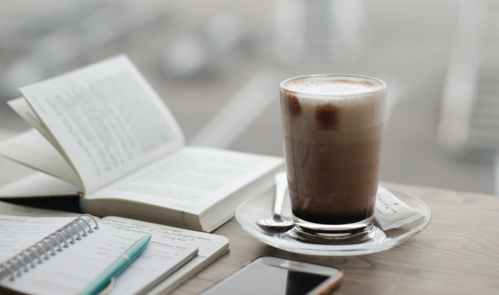 An image of two open books and a cup of coffee on a wooden table.