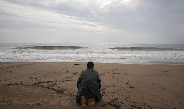 An image of a person sitting on a beach, looking toward the ocean.