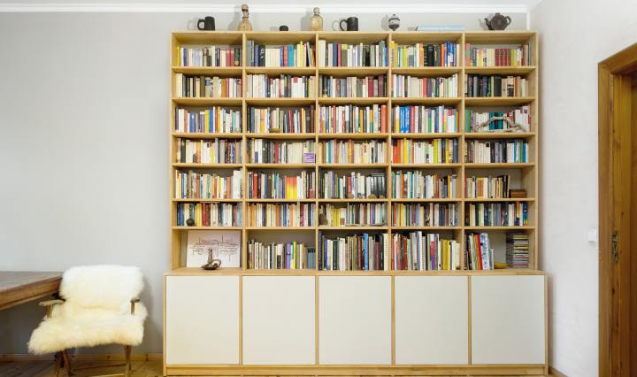 An image of a large wooden bookshelf filled with books, with a small chair beside it.