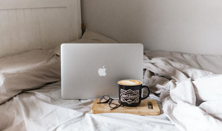 An image of a macbook and a cup of coffee atop an unmade bed.
