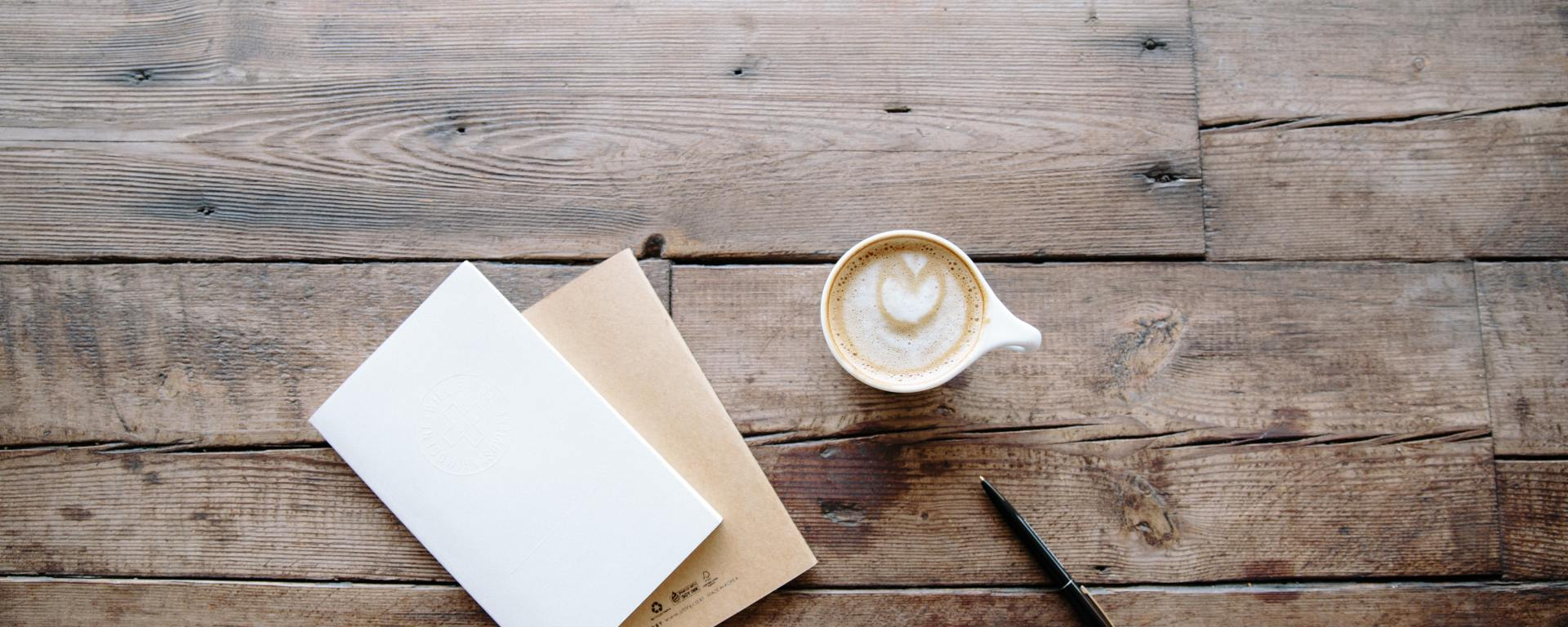 An image of a cup of coffee and two notebooks on a wooden table.