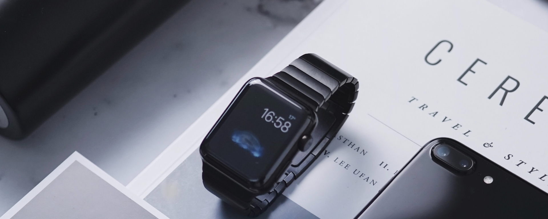 An image of a watch on top of a magazine, next to an iphone.