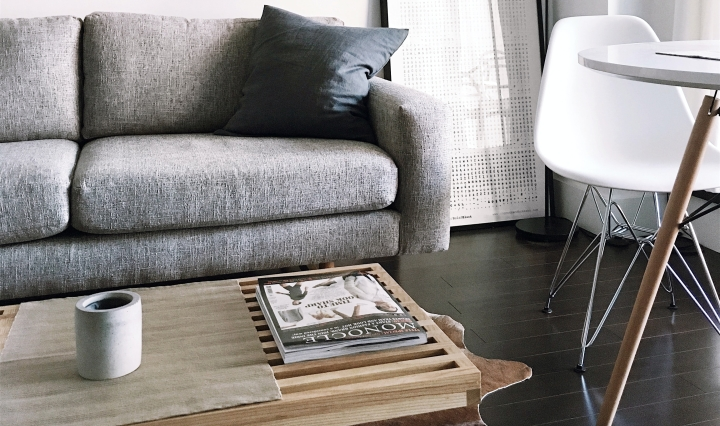 An image of a sofa and wooden table in a clean, tidy interior.