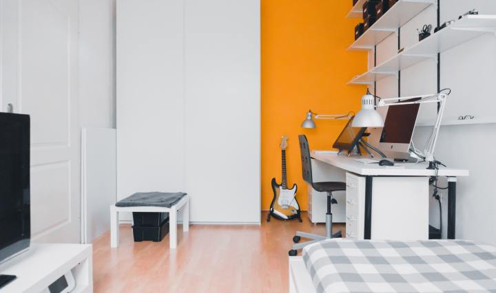 An image of a bedroom with small office space, electric guitar, and minimal furnishings.