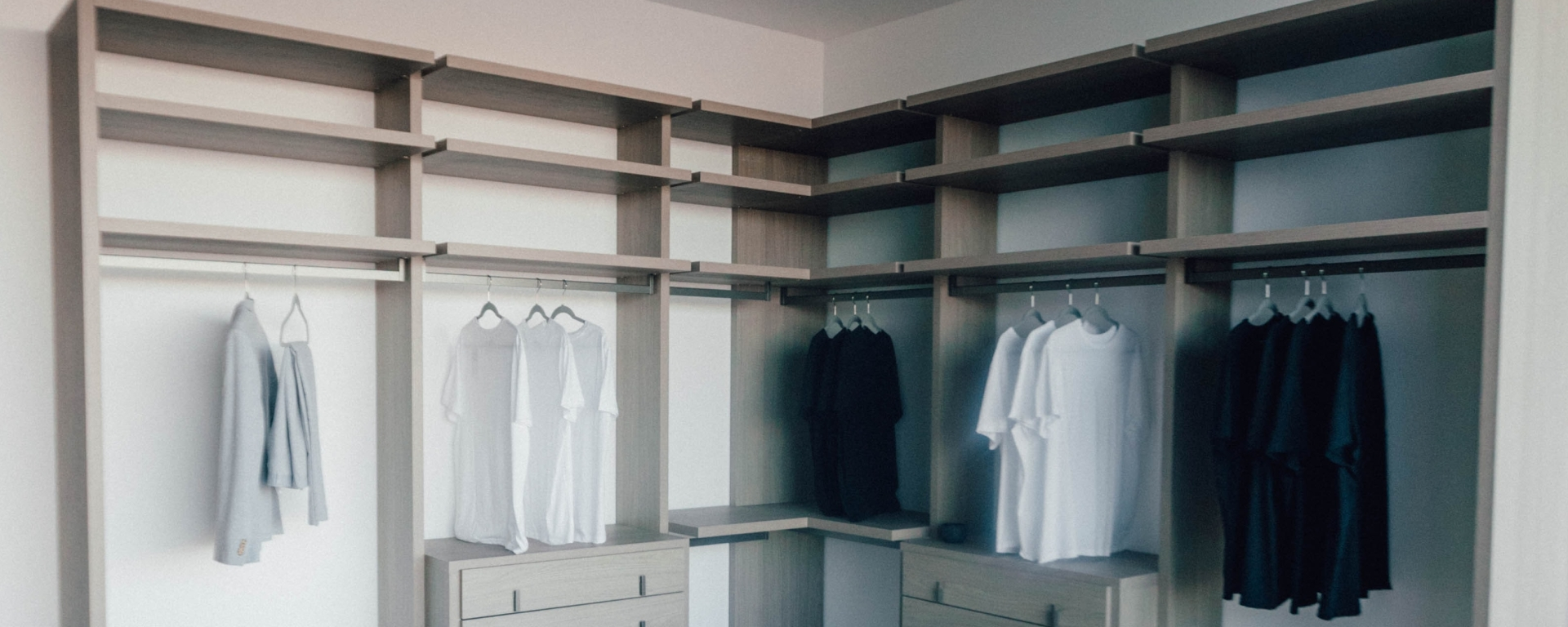 An image of an open closet unit with monochrome clothing on hangers.