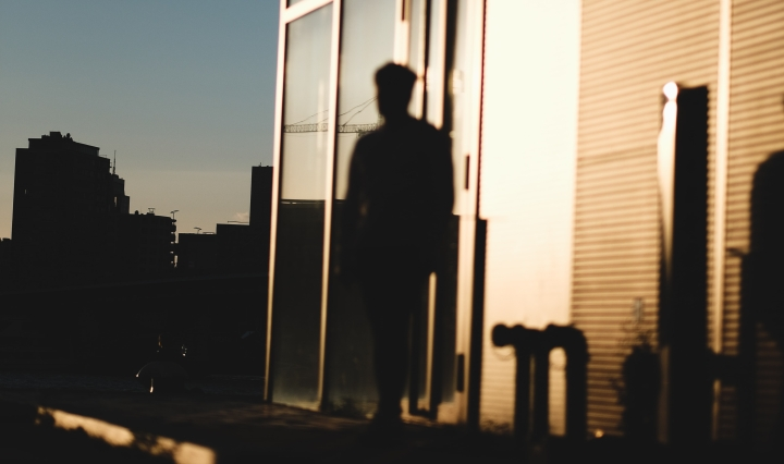 An image of a person, silhouetted, in front of a building in bright sunshine.