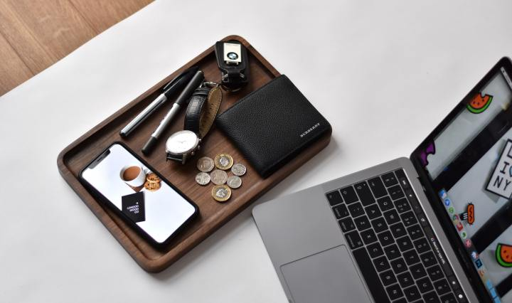 An image of a phone, watch, wallet and coins beside a laptop on a white surface.