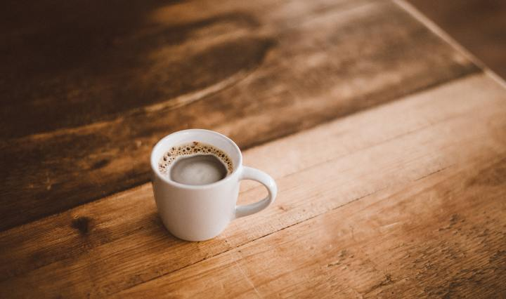 An image of a mug of coffee on a wooden surface.