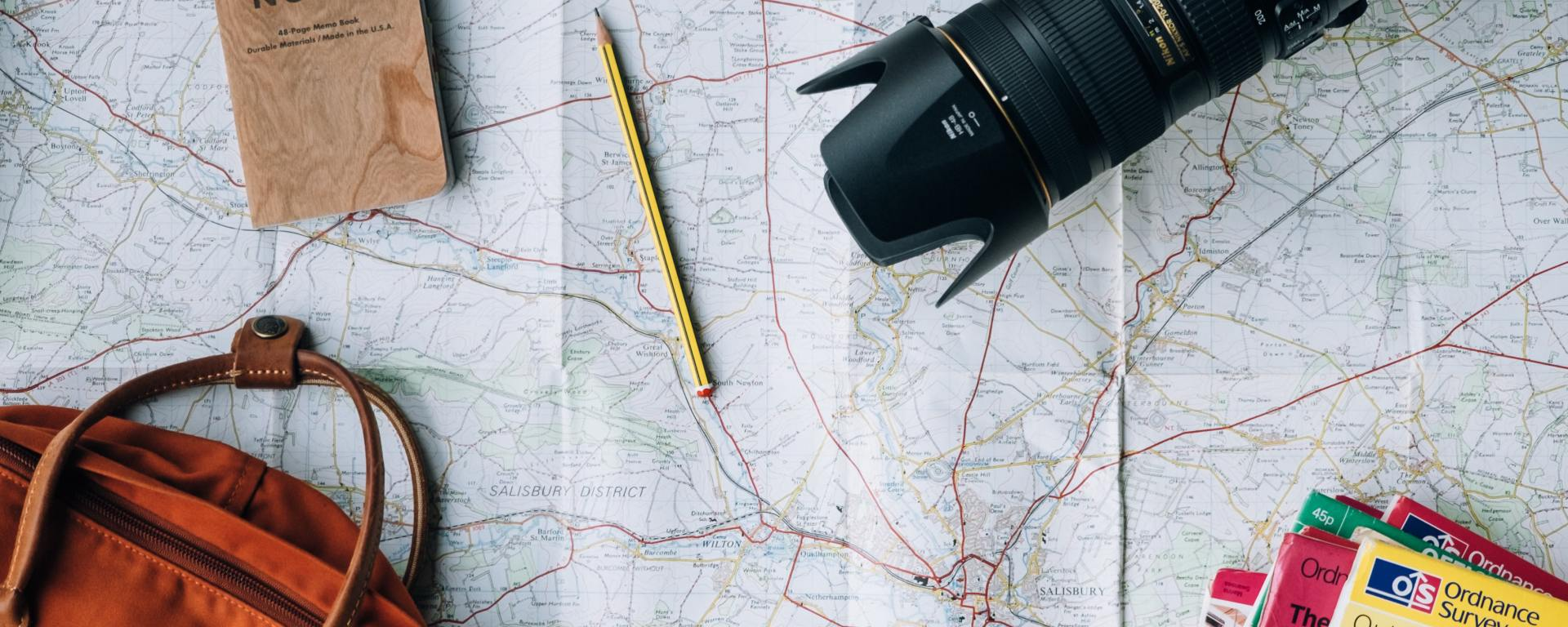 An image of a large map with a backpack, maps, notebook, and camera on top of it.