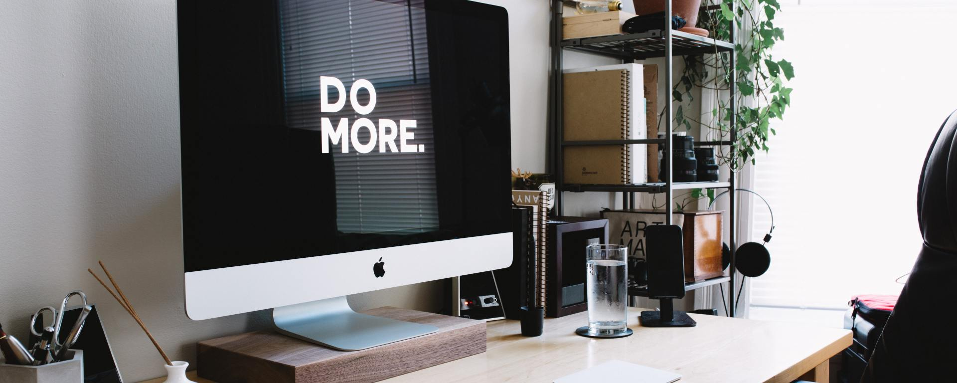 An image of a mac with the slogan 'do more' on screen, on a clean desk with shelving units.