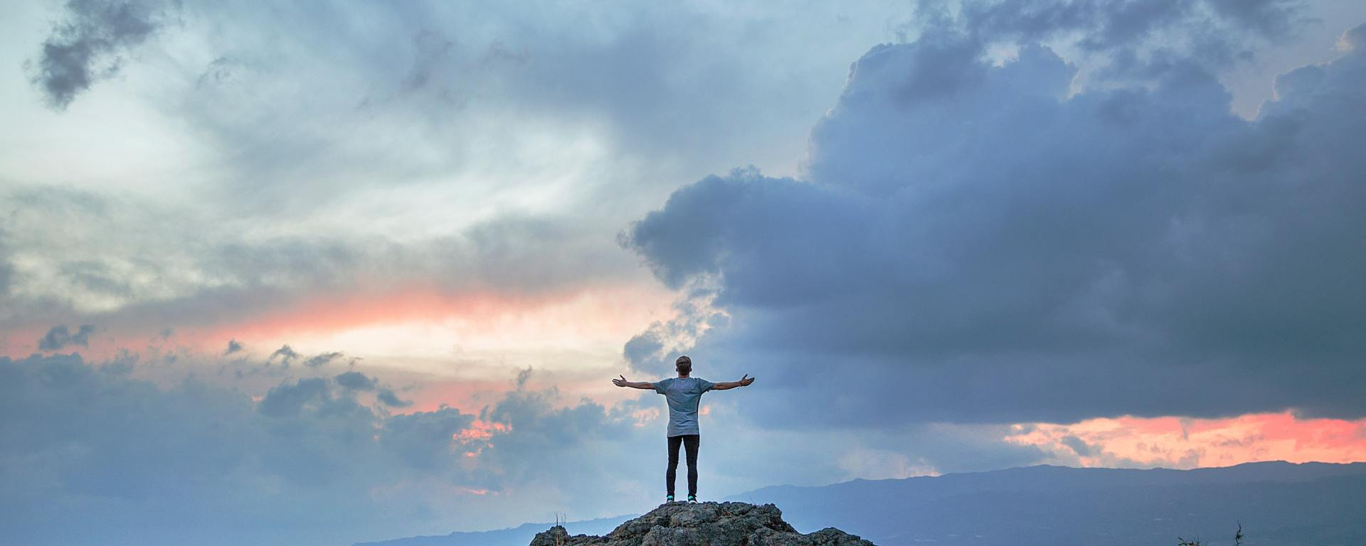 An image of a man on a cliff, holding out his arms to the sky.