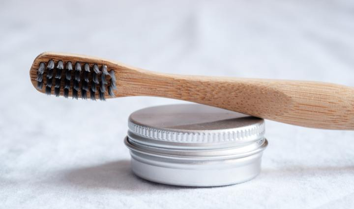 An image of a bamboo toothbrush resting on a small aluminium tin.