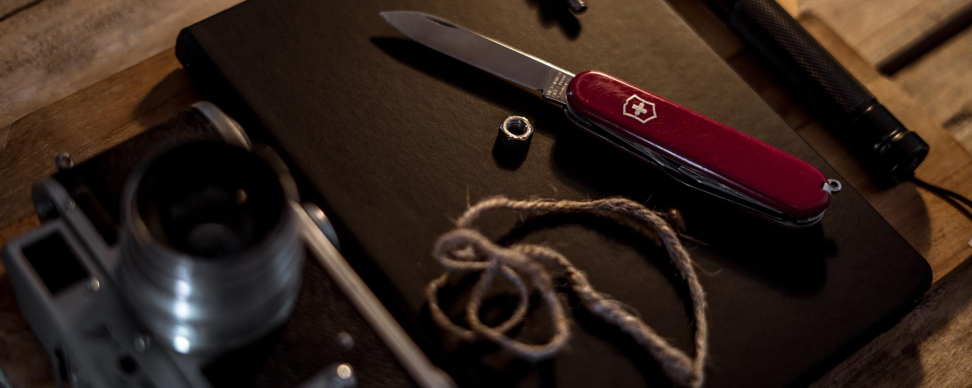 An image of a pocket knife, torch, piece of string, camera and notebook, on top of a wooden surface.