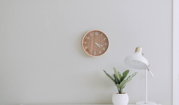 An image of a clock on a wall, a plant and lamp on a desk below.