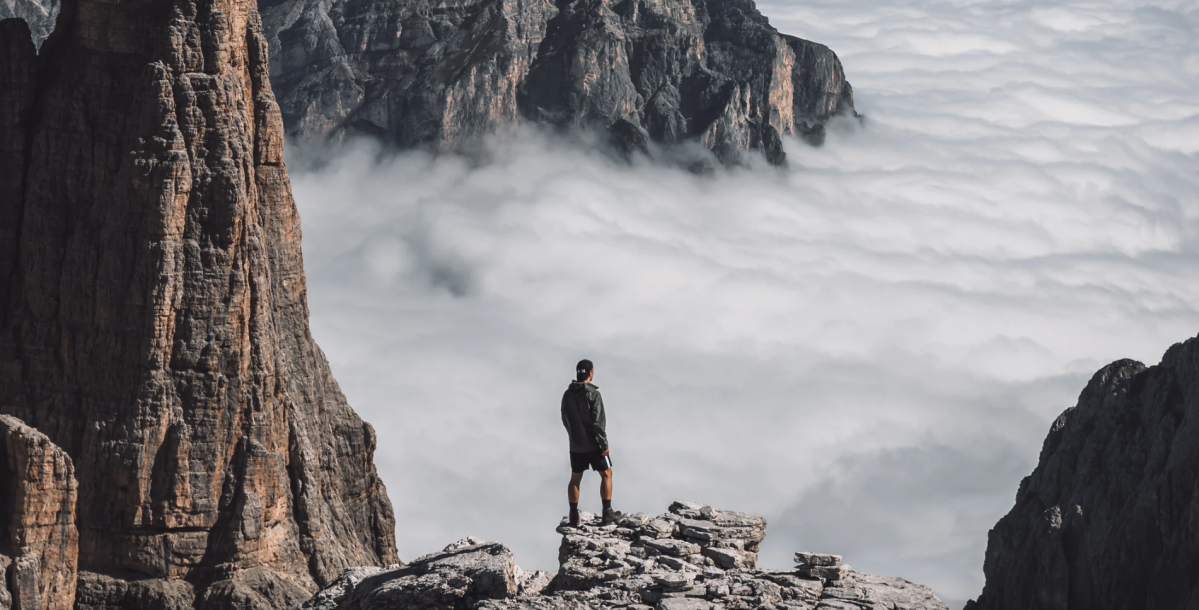 An image of a person standing on a clifftop overlooking fog and clouds.