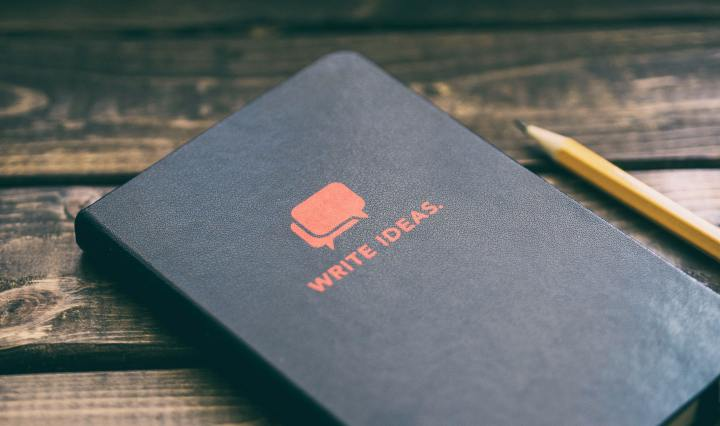 An image of a notebook with the slogan 'write ideas' on a wooden surface.