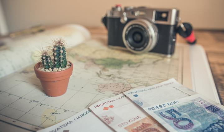 An image of a camera, money, and cactus, on top of a map.