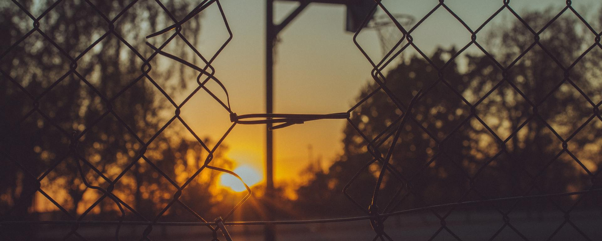An image of a basketball court and sunset beyond a chain link fence.
