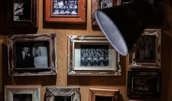 An image of old framed photos on a wall behind a lamp.