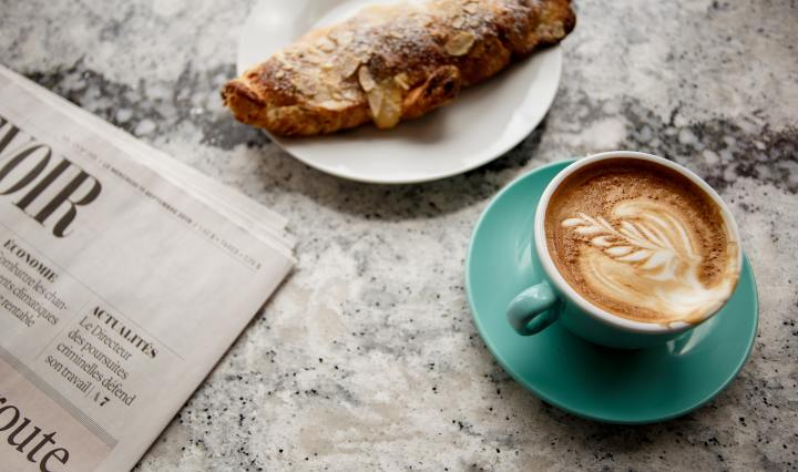 An image of a cup of coffee, croissant, and newspaper on a granite surface.