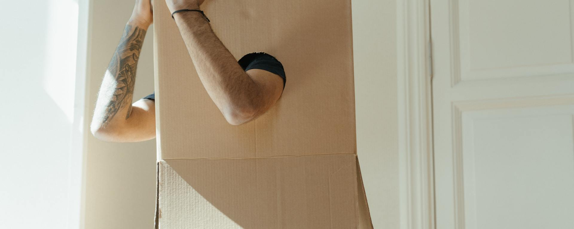 An image of a person in a box, with their face not showing but their arms out.