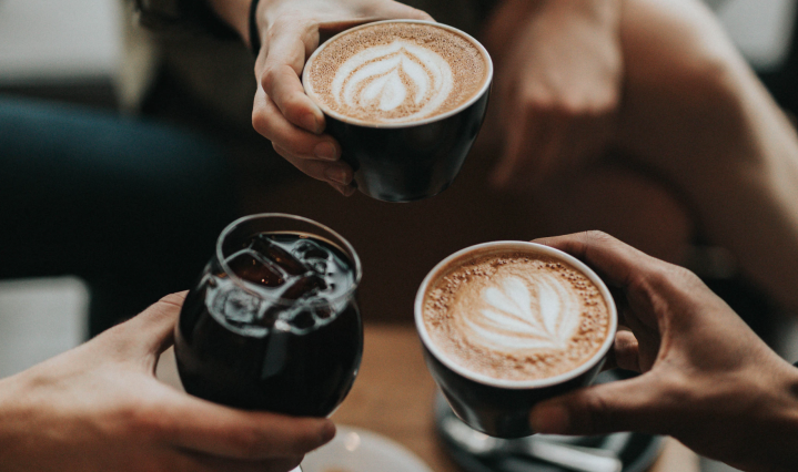 An image of three people holding drinks, two coffees and a soda in cups.
