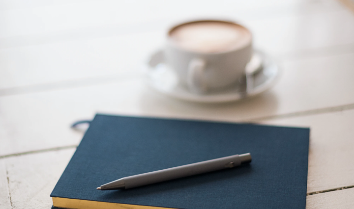 An image of a notebook and cup of coffee on a wooden surface.