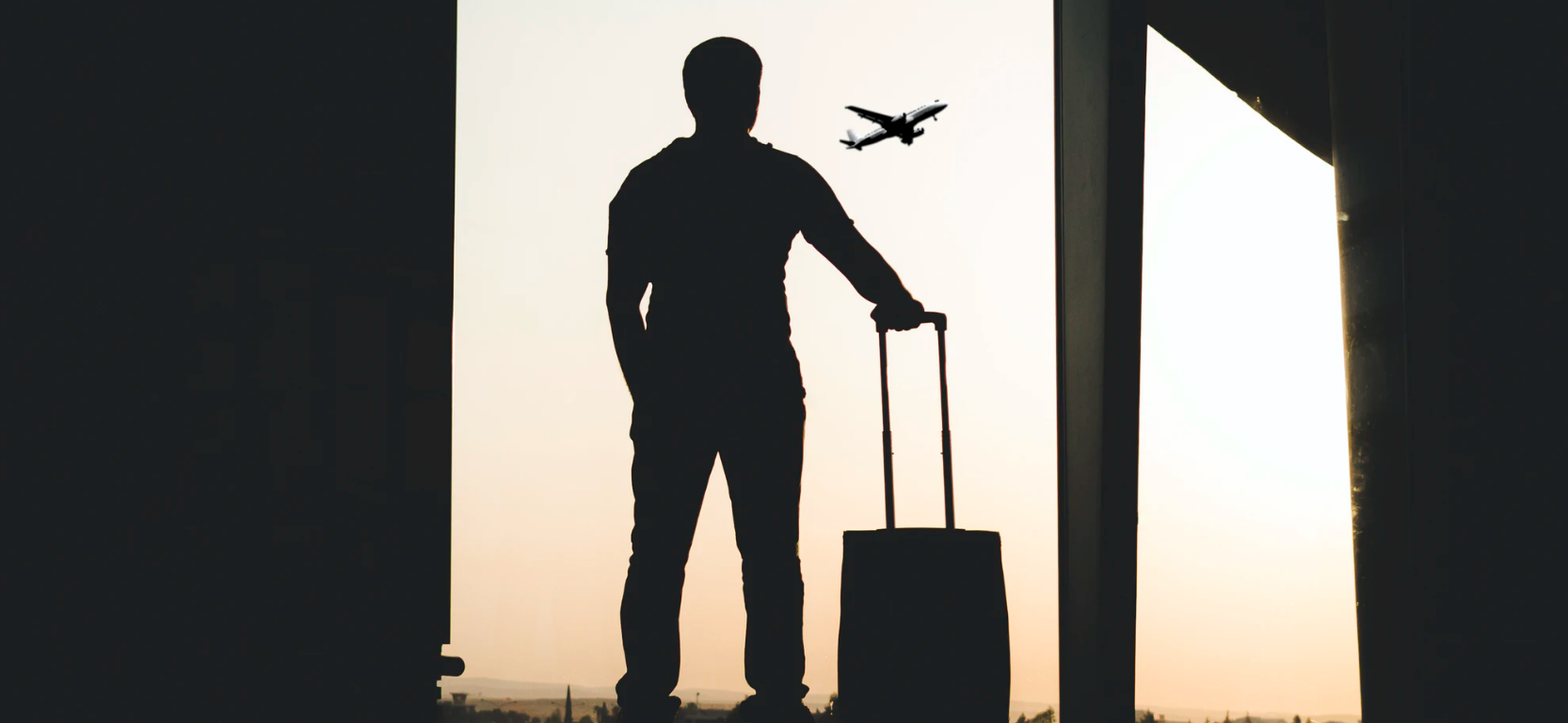 An image of a silhouette of a person with a suitcase and a plane flying in the background.