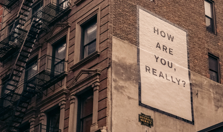 An image of a sign on a building saying, 'how are you, really?'.