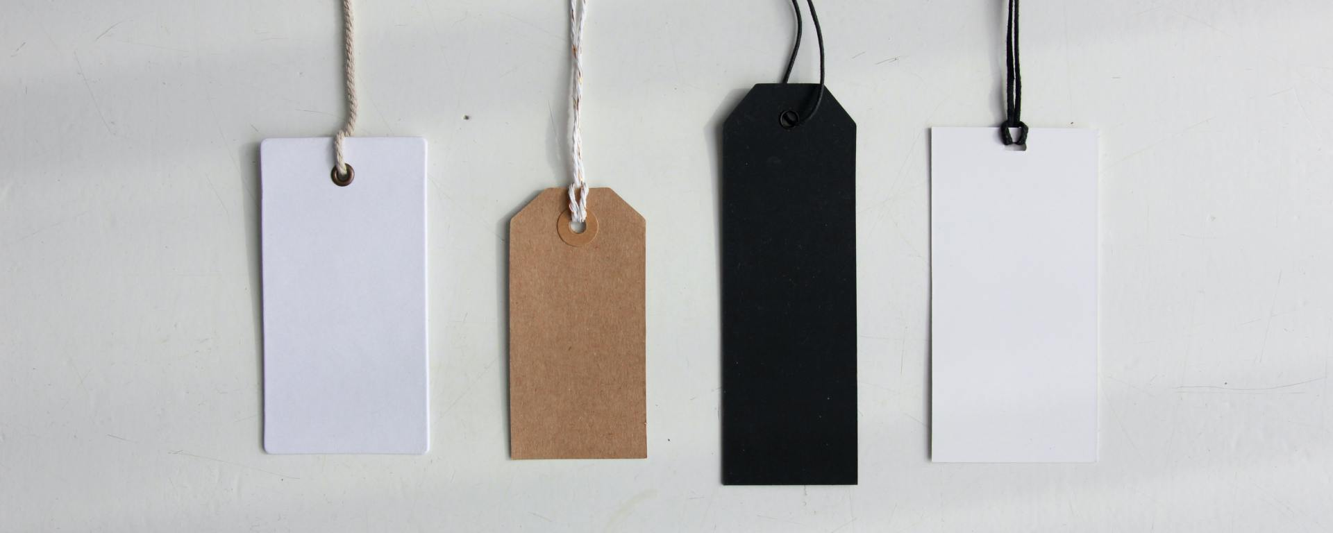 An image of four blank price or gift tags on a plain background.