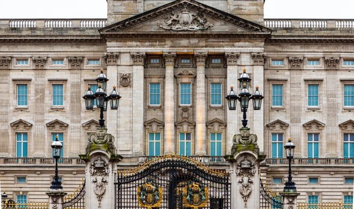 An image of the exterior of Buckingham Palace, from the gates.