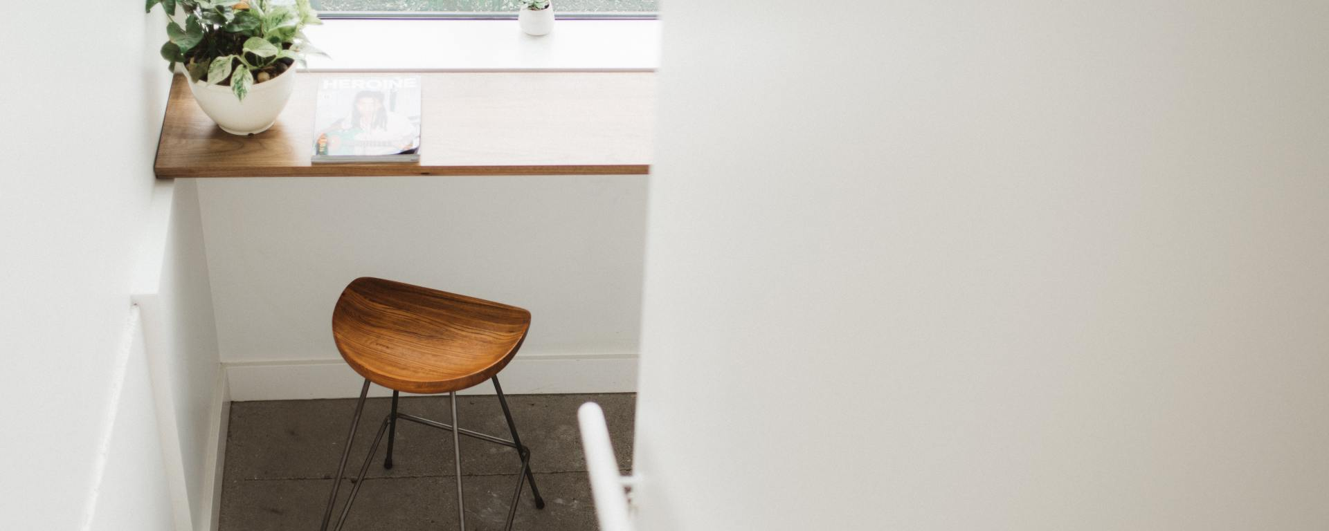 An image of a small wooden stool at a breakfast bar, with a view looking out through a window.