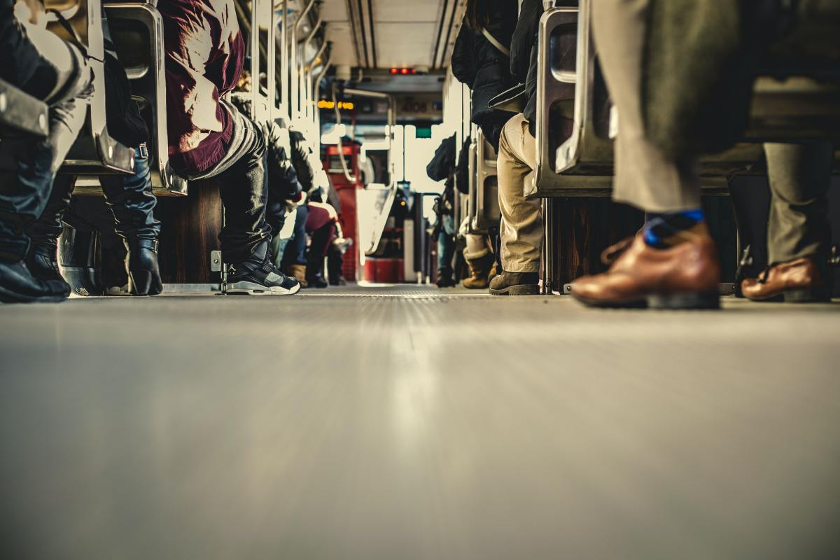 An image of feet on the floor, people in many seats on a bus.