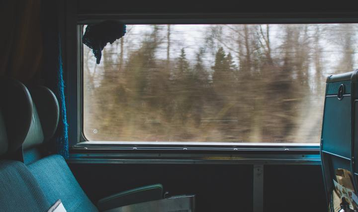 An image of a train interior, the windows looking out onto blurred trees.