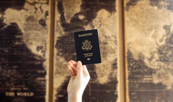 An image of a hand holding up a passport in front of a world map.