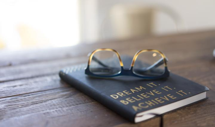 An image of a pair of glasses on top of a notebook with the slogan, 'dream it believe it achieve it'.