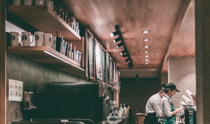 An image of the interior of a Starbucks, toward the end of a counter, with two baristas making drinks.o